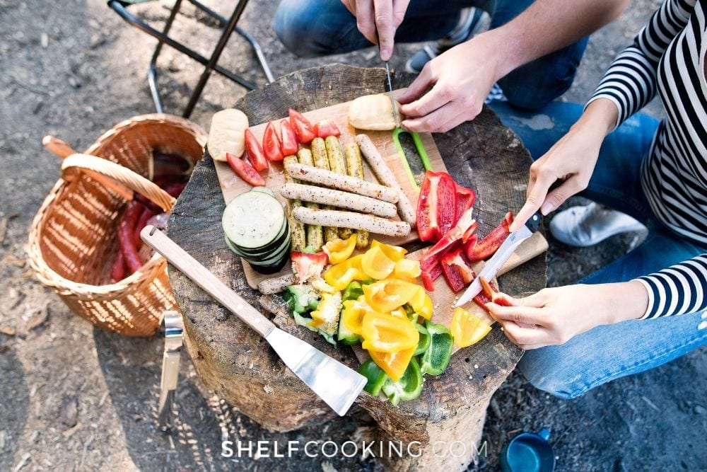 Man and woman chopping veggies on tree stump for make-ahead camping meals from Shelf Cooking.