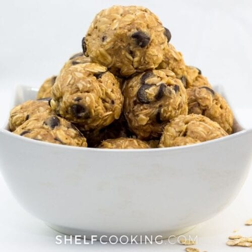No-bake energy bites in a white bowl from Shelf Cooking.