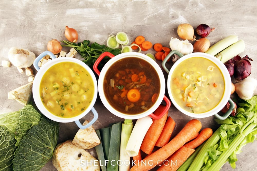 Three bowls of soup surrounded by veggies on counter from Shelf Cooking.