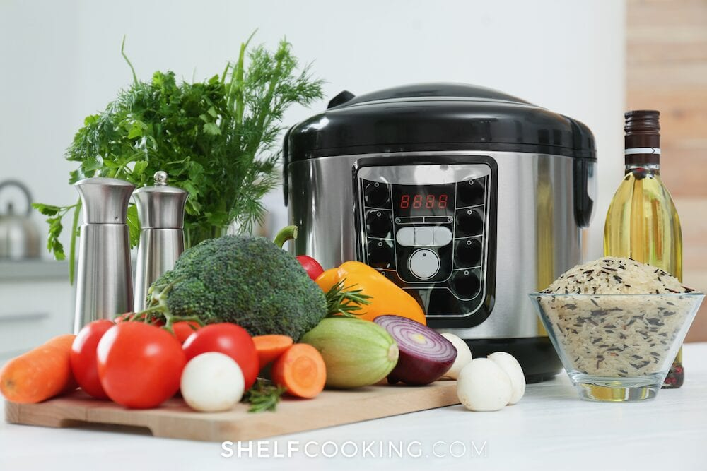 Instant Pot on a table with vegetables from Shelf Cooking.