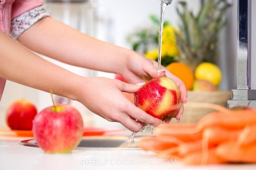 Hands washing an apple in sink for weekly meal prep from Shelf Cooking.