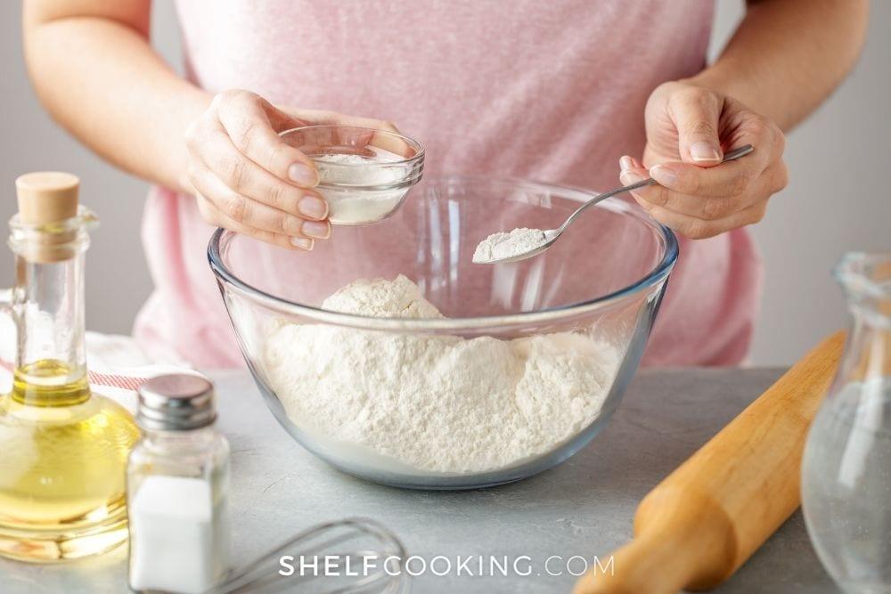 woman adding baking powder to bowl, from Shelf Cooking