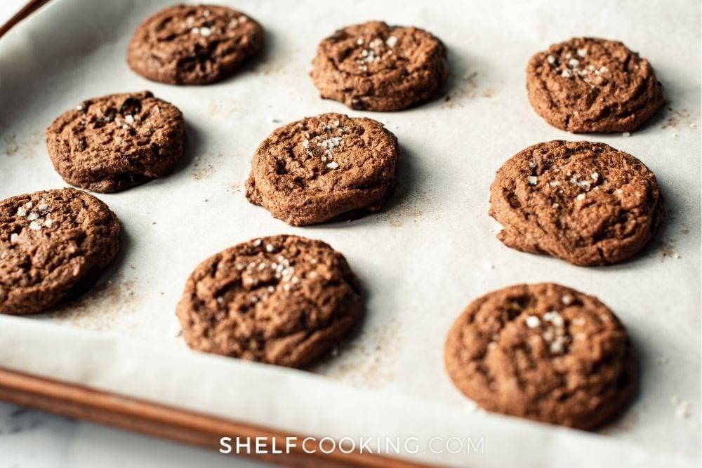 Cookies on a baking sheet with parchment paper from Shelf Cooking.
