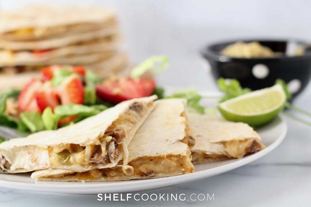 Steak quesadillas on a plate with lime from Shelf Cooking.
