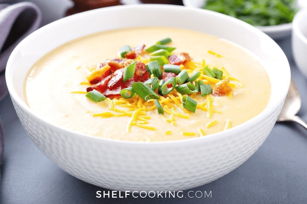 Bowl of potato soup with bacon, cheese, and chives from Shelf Cooking.