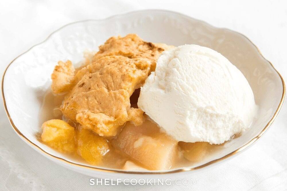 Peach cobbler and ice cream in a bowl from Shelf Cooking.