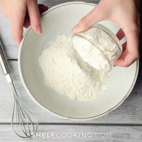 Hand mixing Bisquick substitute ingredients in a bowl from Shelf Cooking.