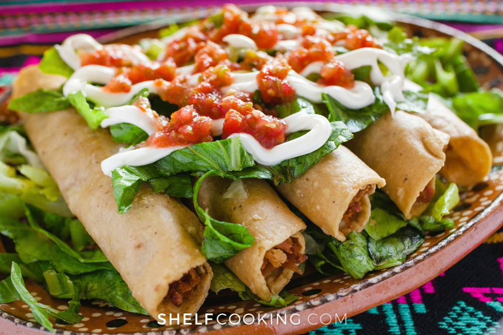 Taquitos with lettuce, sour cream, and salsa on top from Shelf Cooking.