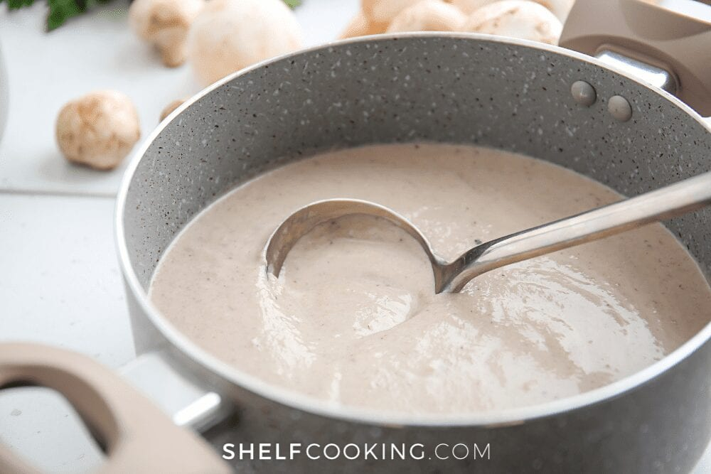 Homemade cream of mushroom soup in a pot from Shelf Cooking.